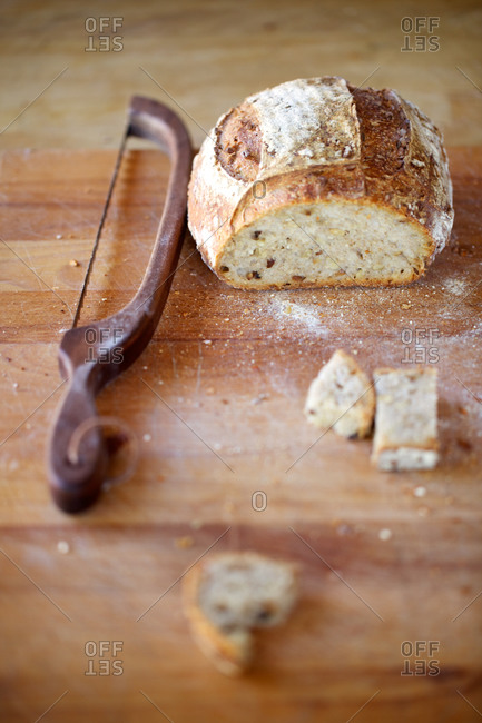 Handmade grain sourdough bread on wooden kitchen counter and bread saw