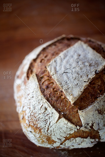 Close-up of handmade whole grain sourdough bread on wooden kitchen counter