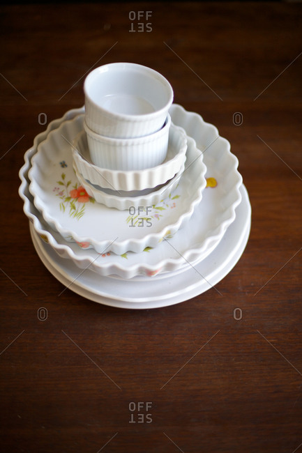 White vintage stacked dishes on a wooden surface