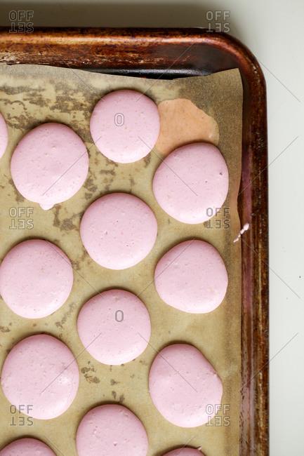 Pink macaroon dough on baking sheet
