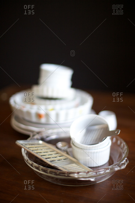 White vintage stacked dishes and graters on a wooden surface