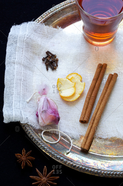 Glass of tea of cinnamon sticks, lemon peel, teabag, cloves, and anise