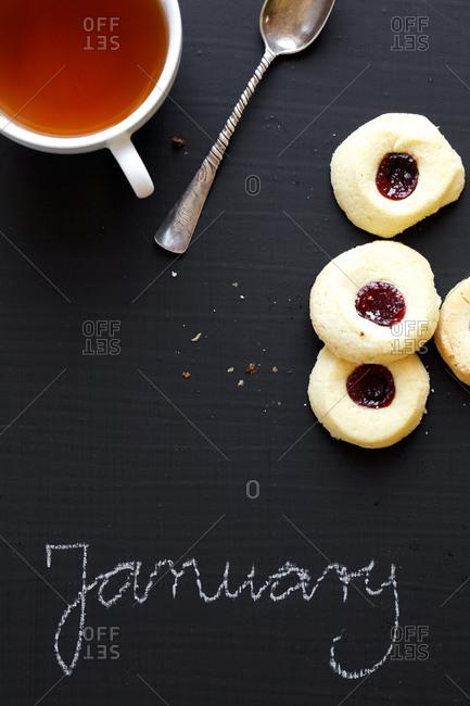 Tea, cookies and January word written on blackboard