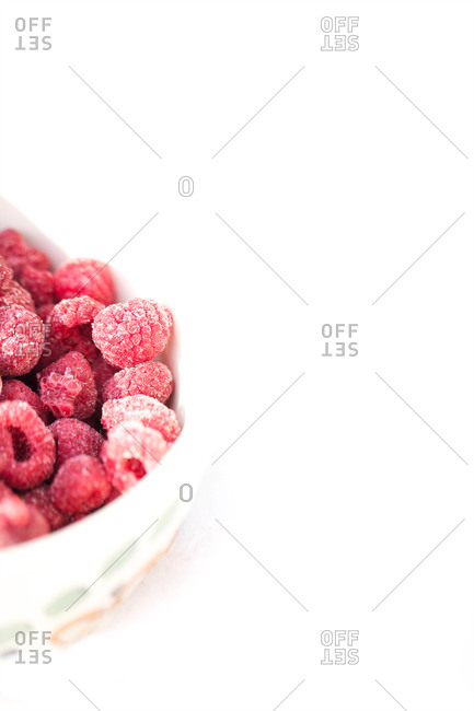 Frozen raspberries in a bowl isolated on white background