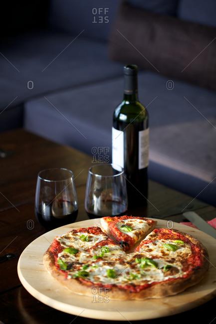 Mozzarella tomato basil pizza served with red wine