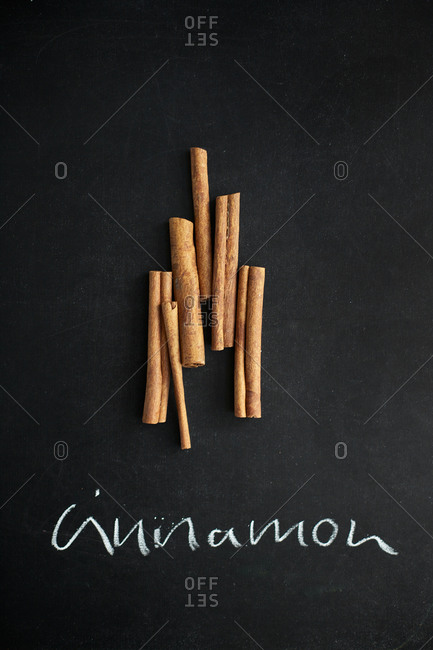 Cinnamon sticks arranged on chalk board with sign