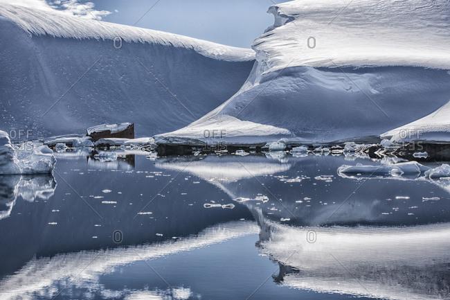 Ice shelf protruding into the ocean close to a shipwreck