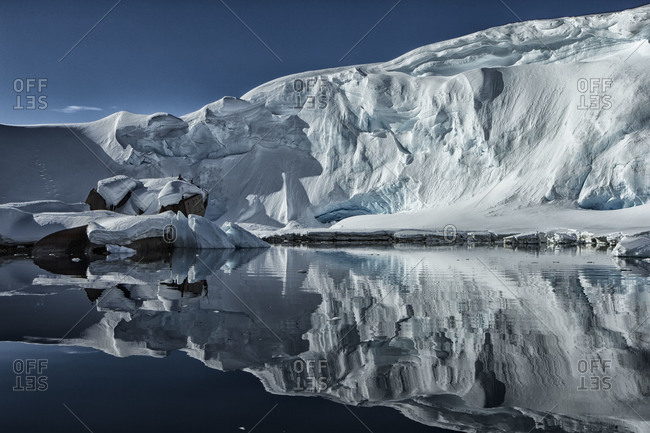 Ice shelf protruding into the ocean close to a shipwreck on a clear day