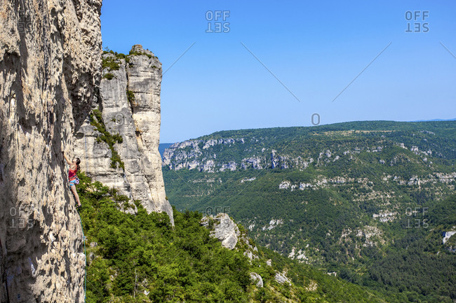 A wide angle perspective of a woman venturing up on a demanding limestone crag.