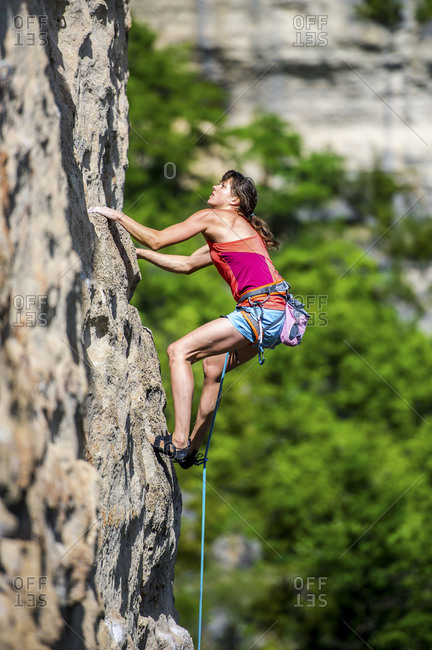 A close up view of a woman venturing up on a demanding limestone crag.