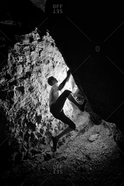 A silhouette of a climber venturing up difficult rock features inside cave in Hameln, Germany.