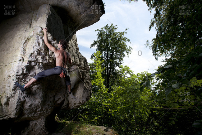 A male climber ascents a protruding rock feature of previously unknown bouldering problem in Hameln, Germany.