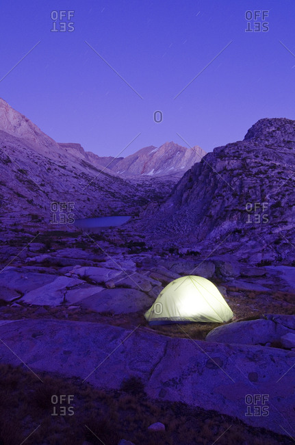 A tent is illuminated at dusk near Cirque Pass on the Sierra High Route, CA.