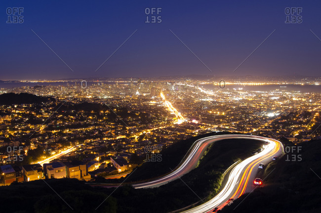 Cars leave a trail of their movement on the winding road up to Twin Peaks with the San Francisco skyline in the background, CA.