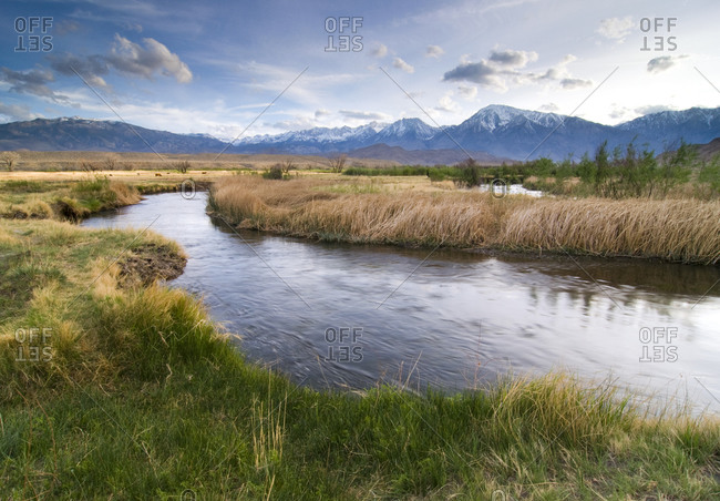 The Owens River winds through a field with the Eastern Sierra mountain range in the background near Bishop, CA.