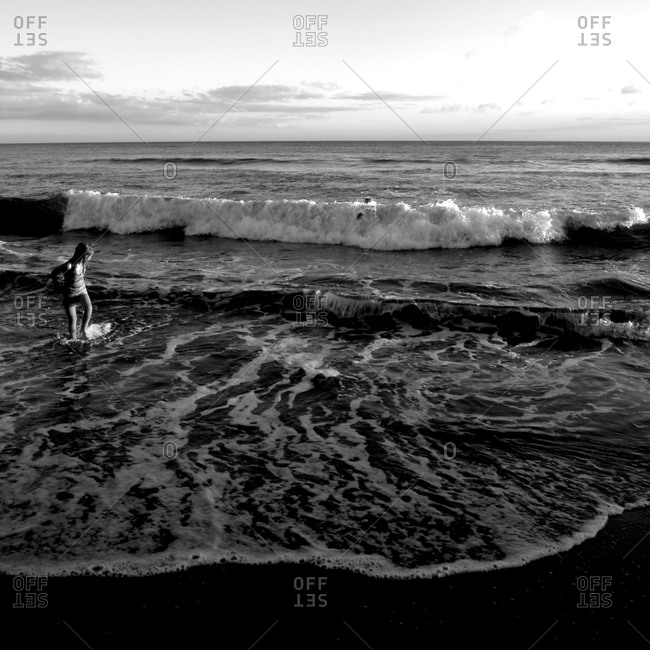 Black & white image of a small child at the ocean shore in Maui.
