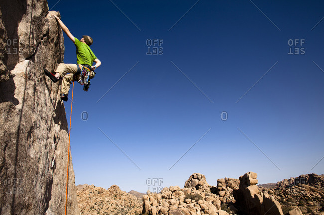 A male climber in a green shirt climbs Sail Away (5.8) in The Real Hidden Valley of Joshua Tree National Park, California.