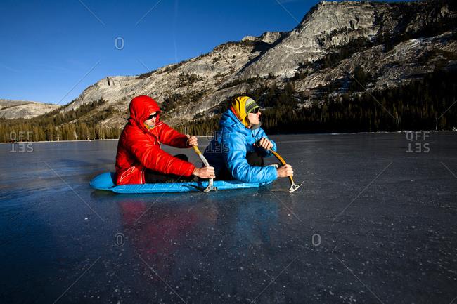 Two men using ice axes to get across Tenaya Lake in Yosemite, California.