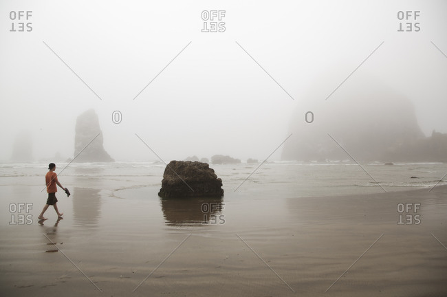 A teenage boy along the beach in the fog during the morning in Cannon Beach, Oregon.