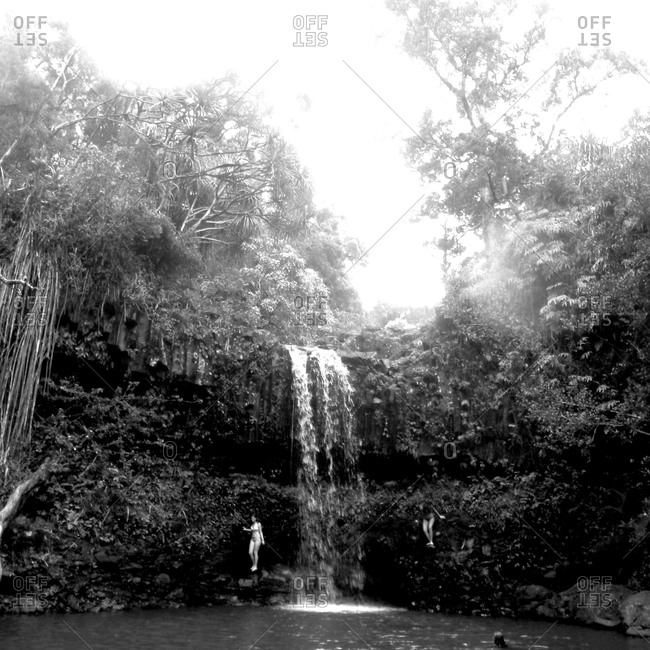 A black & white image of two girls swimming at a waterfall in Maui.