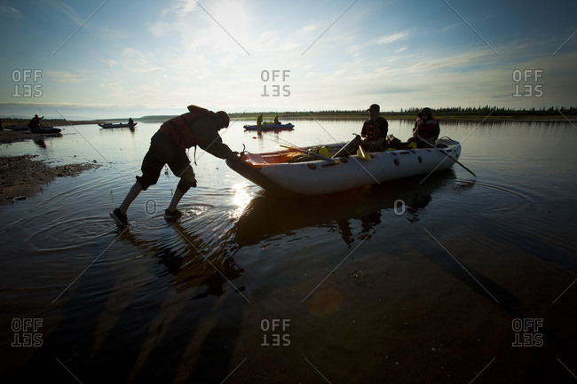 Silhouette of a boy pushing a raft with his friends away from the river bank.