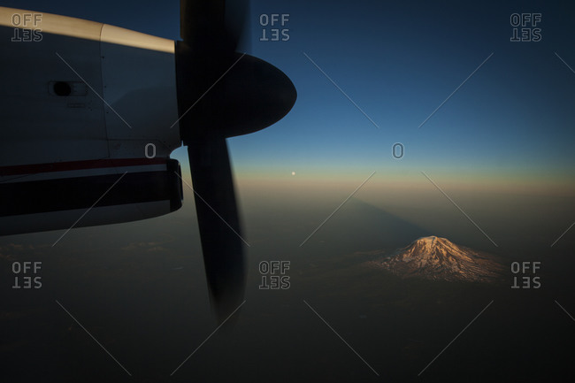A snow capped mountain seen at sunset through an airplane window with the propeller as a frame.