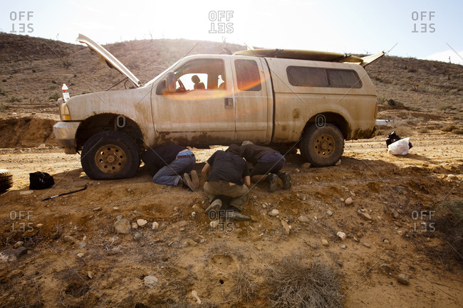 Three male surfers repair a flat tire during a surf trip in Central Baja, Mexico.