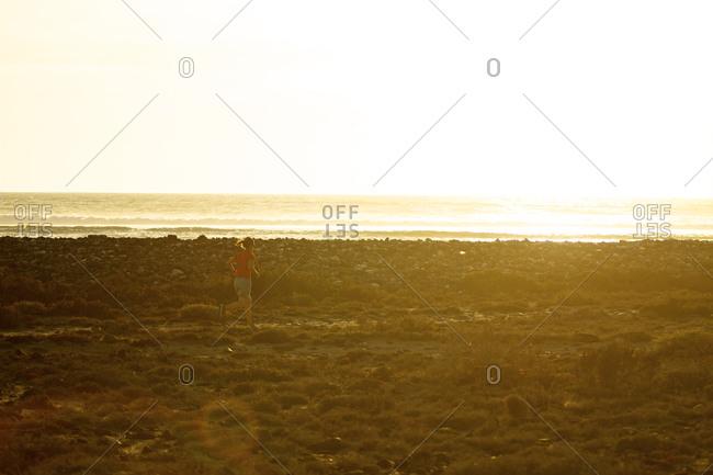 A female running along the shores of the Baja Peninsula. Mexico (Bright, sun flare).