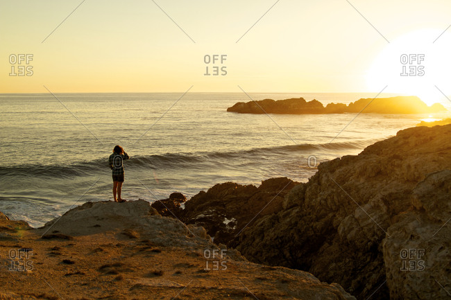 A female stands above a cliff along the rocky shore of the Baja Peninsula watching the sun set behind the ocean's horizon.