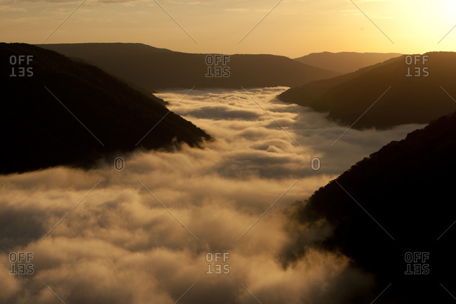 Fog filling a valley in golden light.