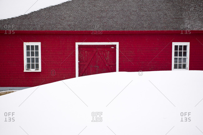 A red barn with white windows and a snow drift in winter in Quebec, Canada.