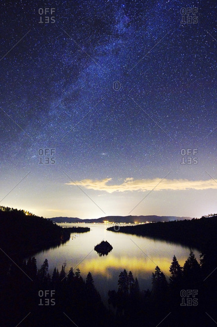 The Milky Way and stars over Emerald Bay at night in Lake Tahoe, CA.