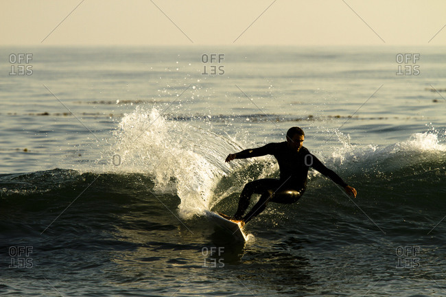 A male surfer rips a turn while surfing in Malibu, California.