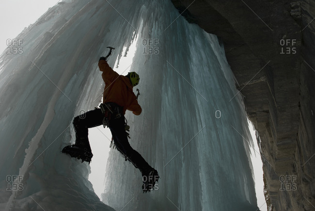 An ice climber tries a new ice climbing route on large, blue, frozen waterfall, Icefield Parkway, Alberta, Canada
