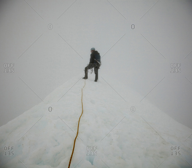 A climber stands on the summit of a peak on a white-out day as clouds surround him