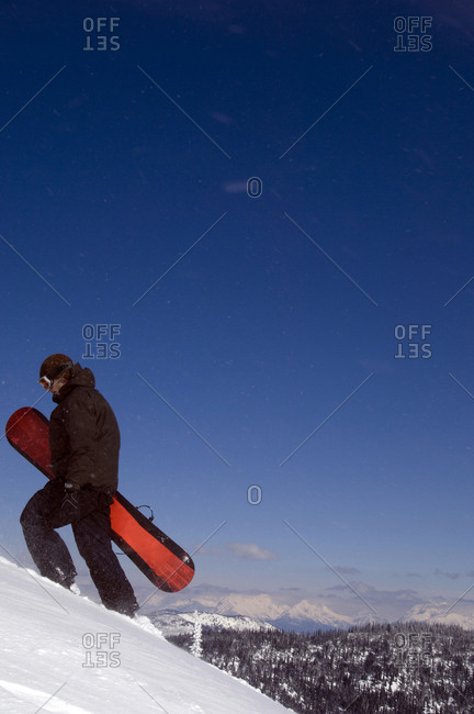 A young man walks up a snowy mountain with his snowboard in the backcountry
