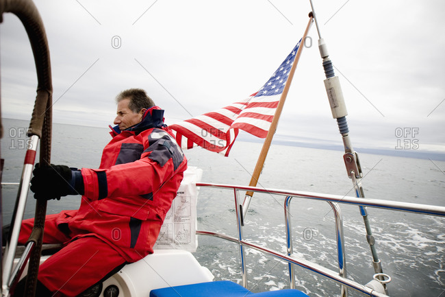 A man steering his sailboat with an American Flag flying in the background