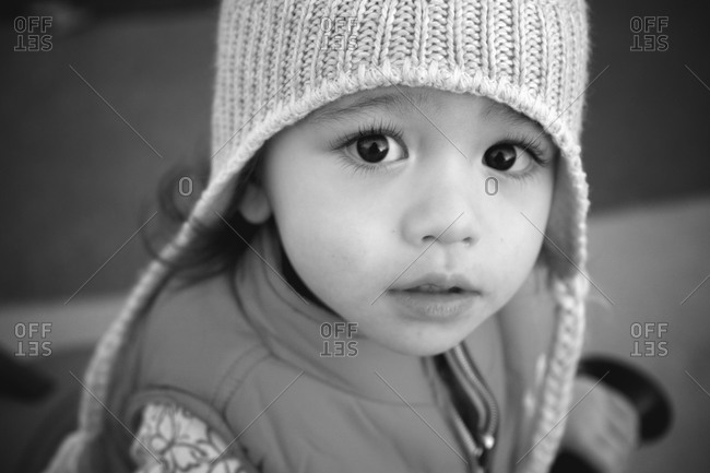 Young girl with big dark eyes wearing a beanie and a vest looks at the camera
