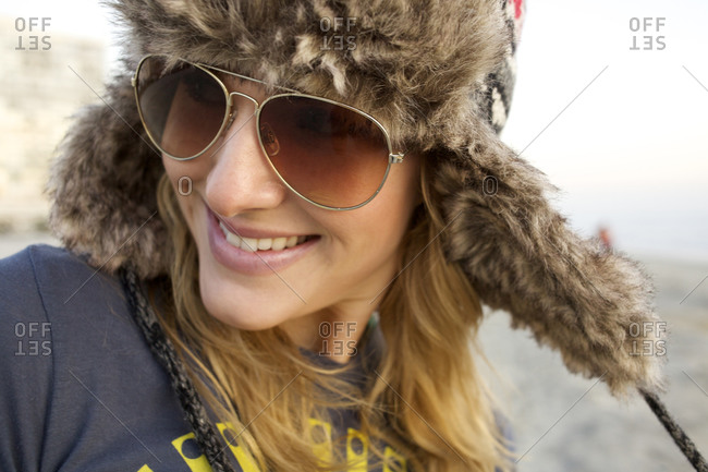 Young female wearing a furry hat and sunglasses looks away from the camera and smiles