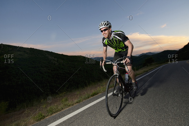 A road biker rides up East Canyon at sunset near Salt Lake City, UT