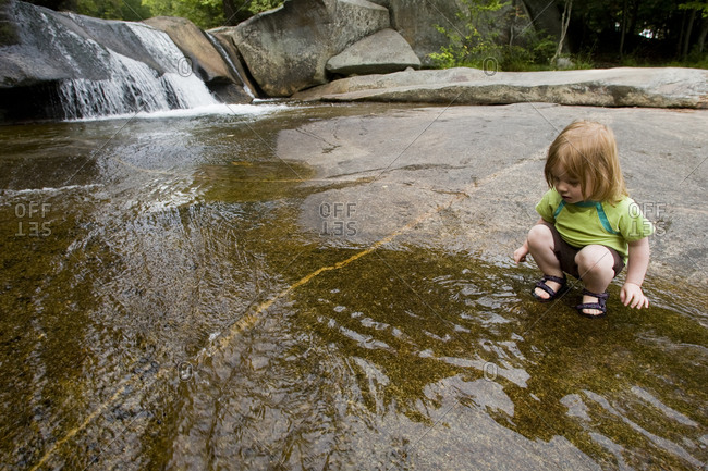 A young girl plays near a waterfall
