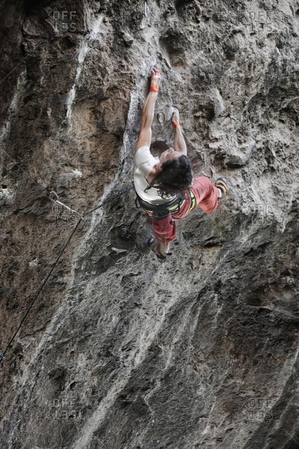 A middle aged woman wearing white tshirt and red pants rock climbing in Jilotepec, Estado de Mexico, Mexico
