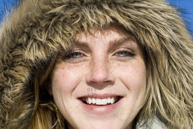 Woman outside wearing furry hood