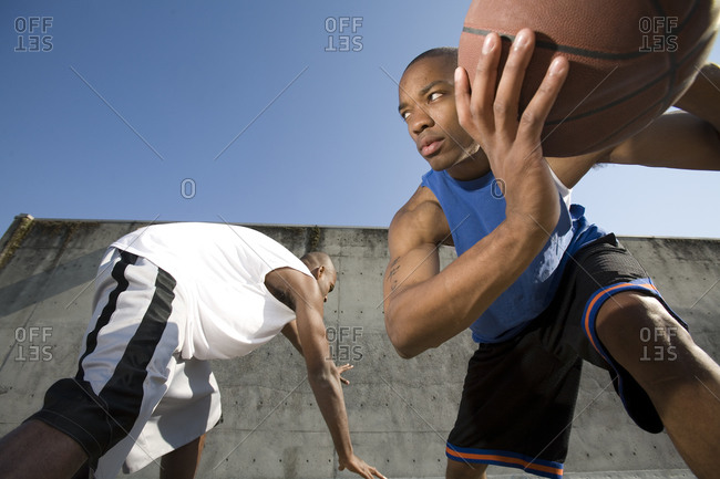 Two men play basketball