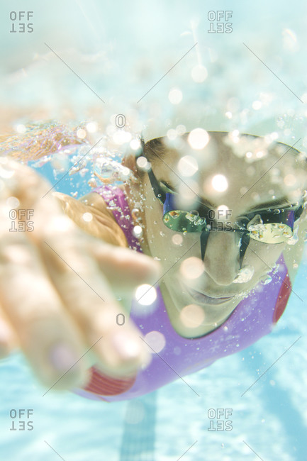 An athletic young woman swimming in a pool as seen from below the water line