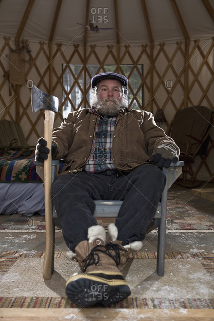 Bearded man with ax in sparse yurt, Whitefish, Montana