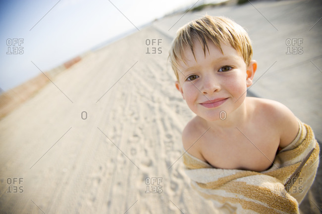 A smiling young boy enjoys a sunny summer afternoon at the beach in Huntington Beach, California