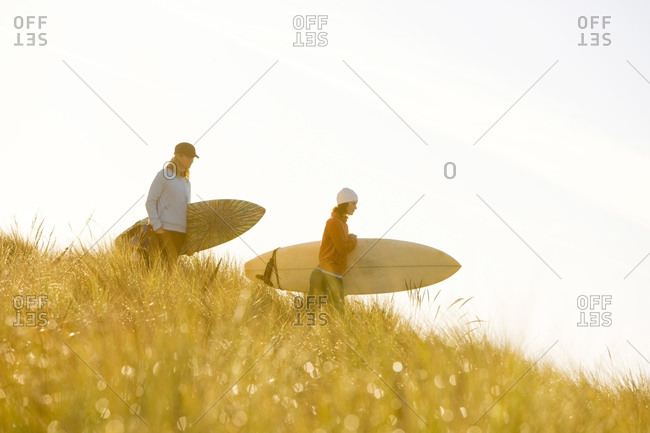 Two women surfers on a sand dune covered with tall native grasses holding their boards as they check out the morning surf