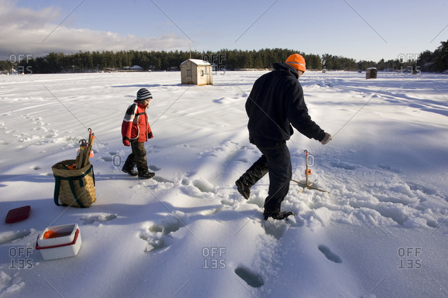 A man teaches a boy how to ice fish on Maine Lake in North Waterboro, Maine