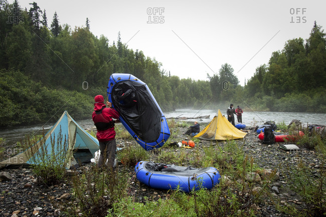 Four friends packing up camp by a river with tents and packrafts in the rain.